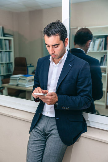 Portrait of handsome businessman looking smartphone in front of office window Business Busy Company Man Suit Working Business Finance And Industry Businessman Caucasian Chairman Chief Concentration Device Executive  Headquarters Jacket Job Male One Person Portrait Serious Smart Phone Sucess Technology Vertical