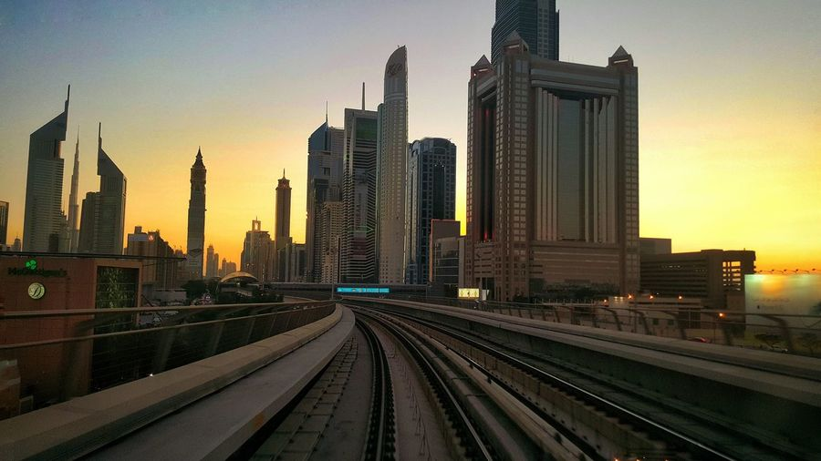 Railroad Tracks In City At Sunset