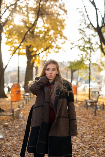 Portrait of woman standing in park during autumn