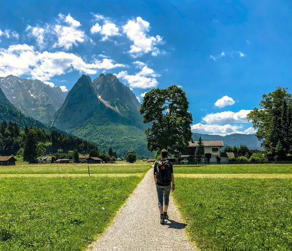 Man walking on a hiking trail facing the mountains Hiking Zugspitze Mountain Range Garmisch-partenkirchen Alpes Plant Sky Green Color Cloud - Sky Nature Real People Beauty In Nature One Person Sunlight Mountain Full Length Field Leisure Activity Land Day Rear View Tree Growth Grass Lifestyles