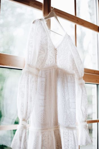Close-Up Of White Dress Hanging By Window At Home