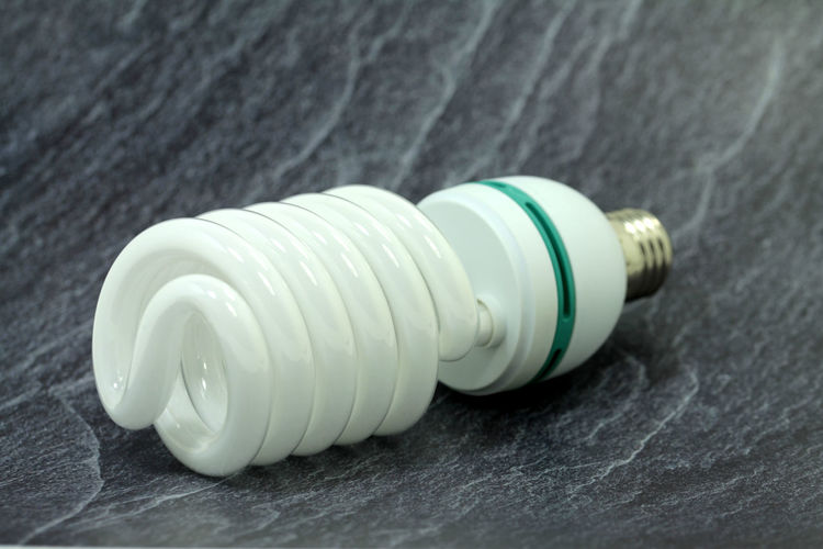 Close-up Indoors  Still Life No People Energy Efficient Table White Color Energy Efficient Lightbulb Spiral Plastic Fuel And Power Generation Single Object Electricity  Simplicity Light Bulb Pattern Lighting Equipment Wood - Material Two Objects High Angle View