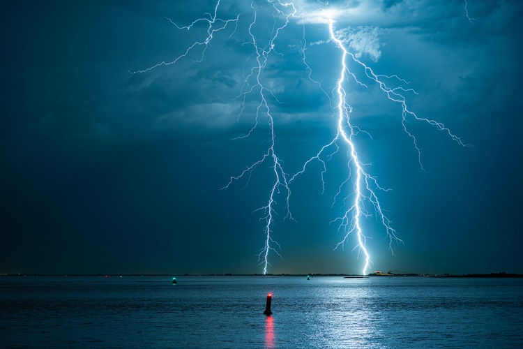 Powerful forked lightning bolts over water
