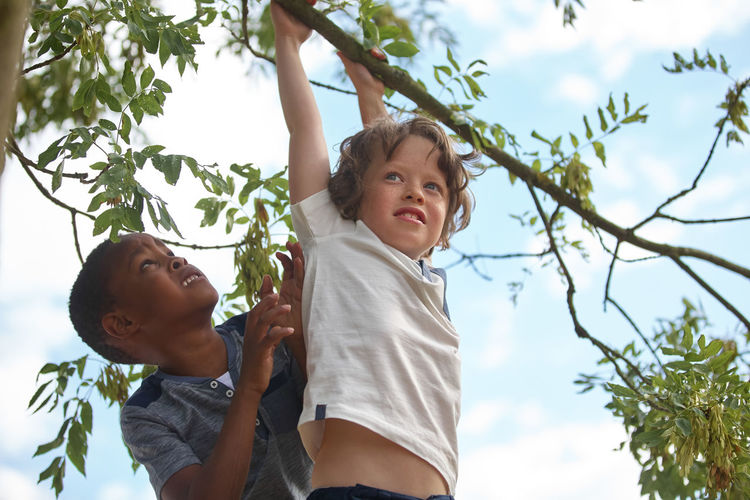 Low Angle View Of Boy Hanging With Male Friend At Park