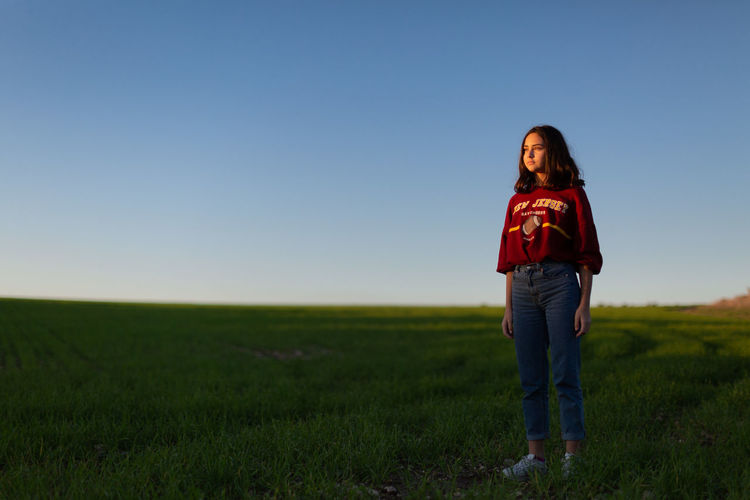 Cute girl standing on grassy field against clear sky