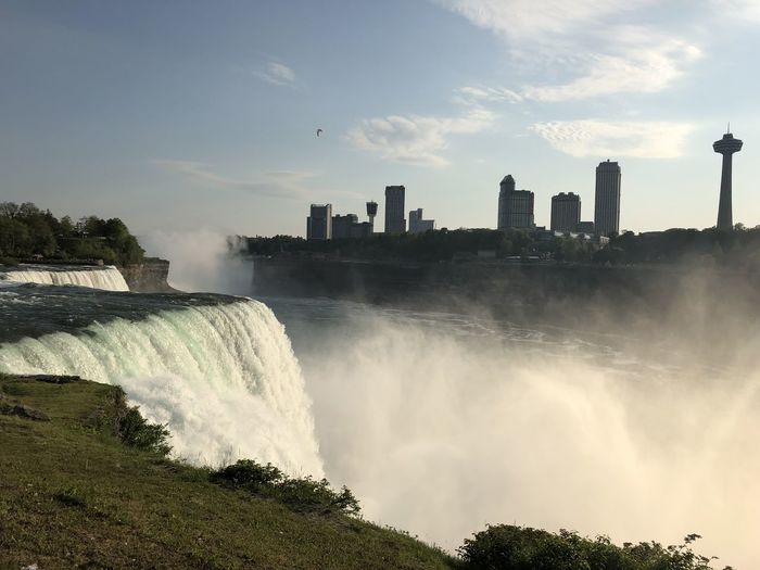 Panoramic view of waterfall in city against sky