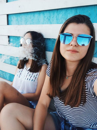 Portrait of smiling woman sitting with friend exhaling smoke