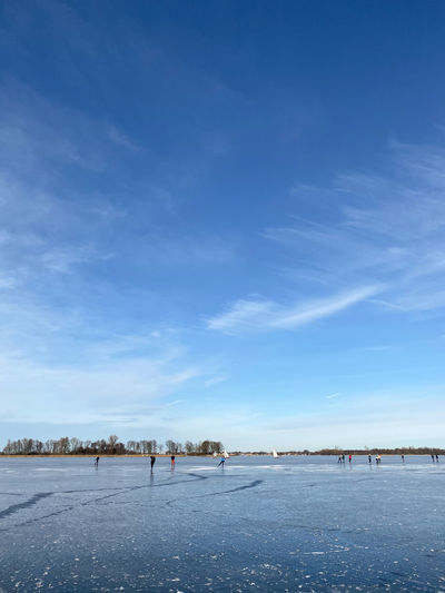 People walking on snow covered land against blue sky