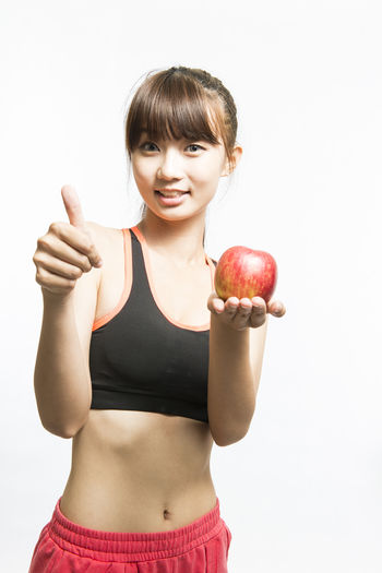 Portrait Of Smiling Woman With Apple Showing Thumbs Up Against White Background