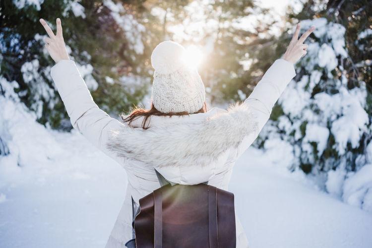 Rear view of woman walking in snow