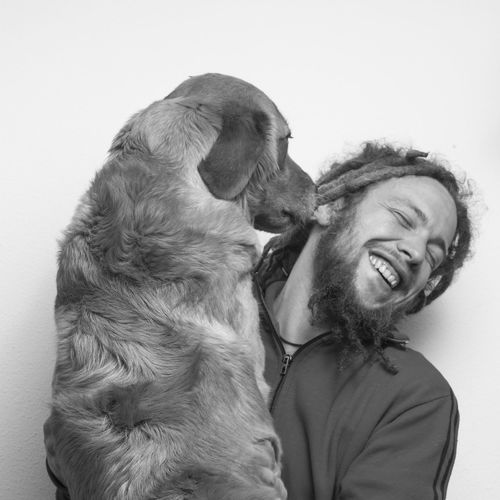 Portrait of man with dog against white background