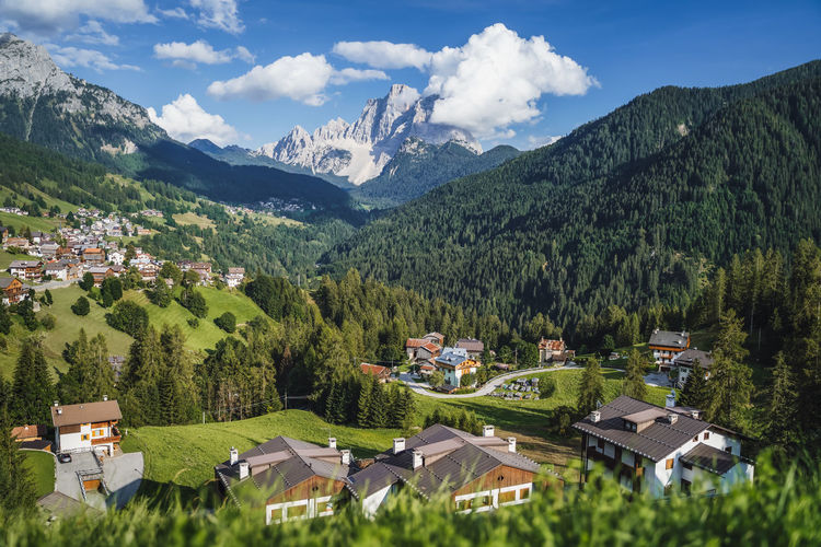 Scenic view of houses and mountains against sky