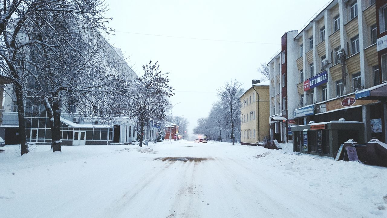 snow, winter, cold temperature, building exterior, weather, architecture, built structure, street, outdoors, clear sky, road, car, bare tree, transportation, nature, the way forward, frozen, tree, no people, day, sky, city