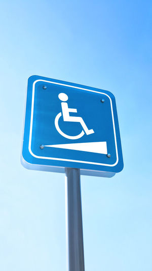 Low angle view of disabled access sign against clear blue sky