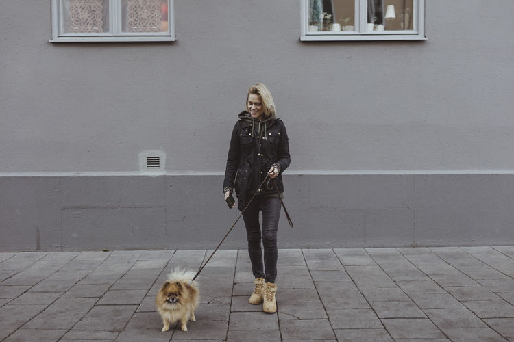 Woman with dog on footpath