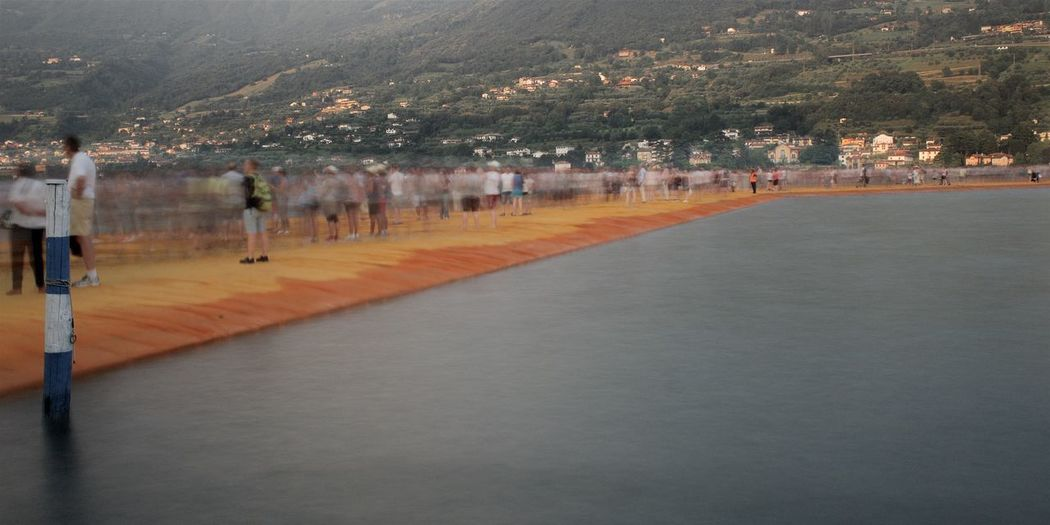 Floating On Water Floating Piers Iseo Lake Italy Brescia 2016 Christo Sulzano City Day Transportation Architecture Nature Mountain Tree Road Outdoors Water Plant Incidental People Built Structure Building Exterior Walking Direction Sign Street Waterfront