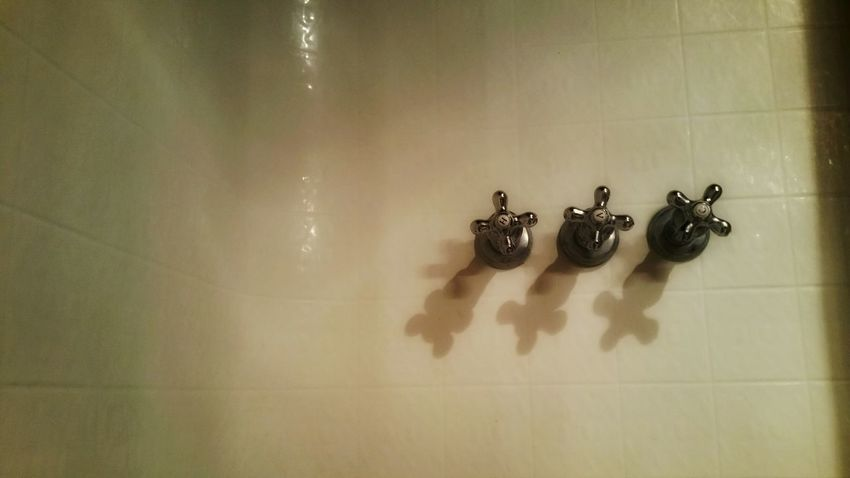 Three faucet knobs. All on a row. Minimalism. White tile background. Knobs Tile White Three Minimalism Right Justified Shiny Bathroom Fixtures Hot Cokd Shower Tub Tub Time Relaxation Zen Atmospheric Solitude