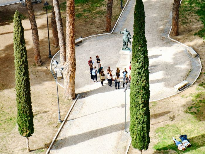High Angle View Of Students Standing By Statue On Footpath In Park