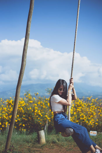 Woman sitting on swing against sky