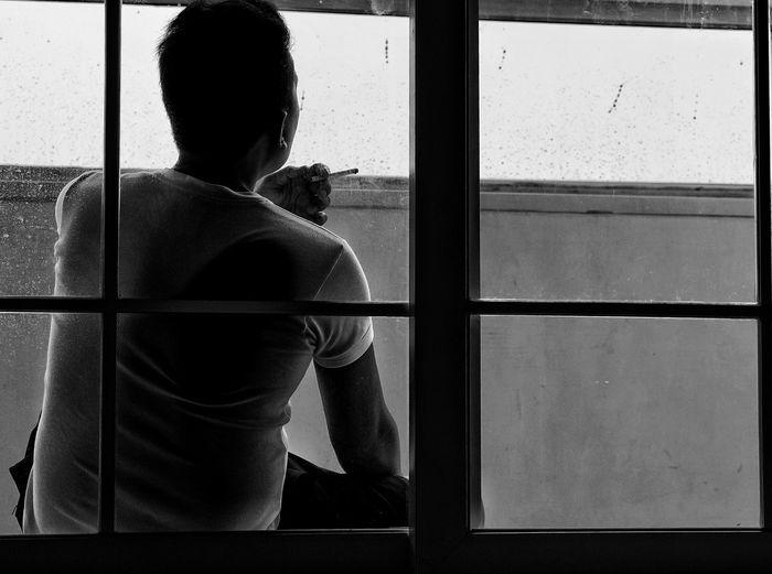 Rear view of man smoking cigarette seen through window