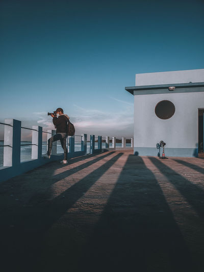 Full length of man photographing while standing by railing against sky