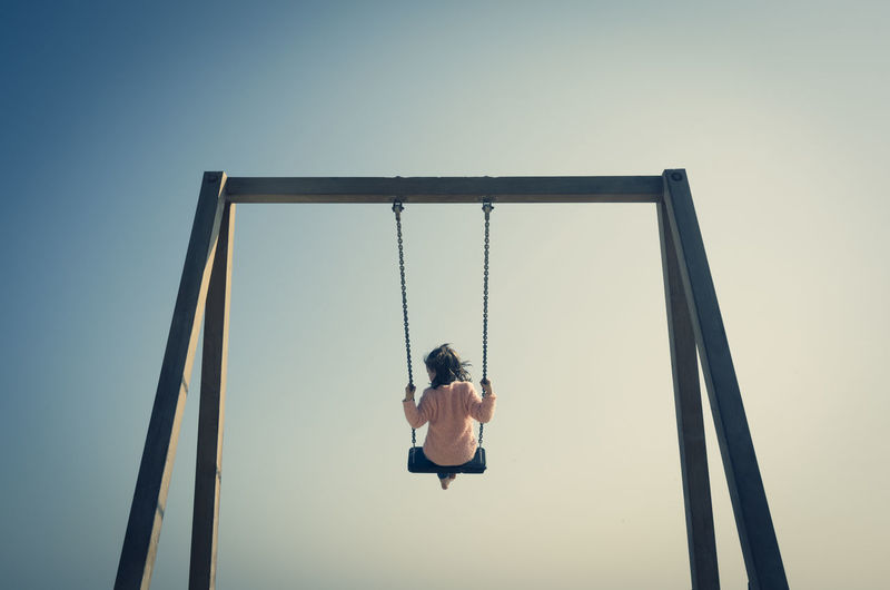 Rear view of girl swinging on swing at playground against clear sky