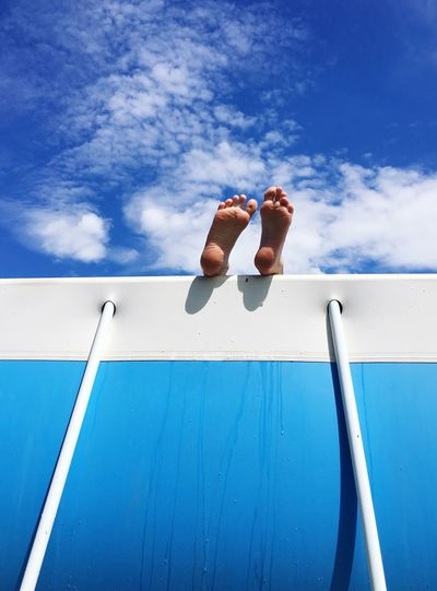 Low section of person resting on boat against sky during sunny day