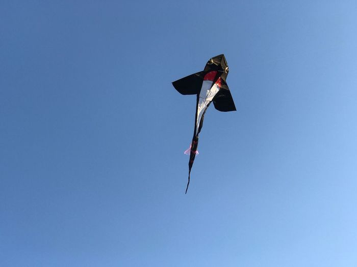 Low angle view of kite against clear blue sky