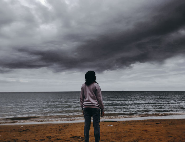 Rear View Of Woman Standing Against Sea At Beach