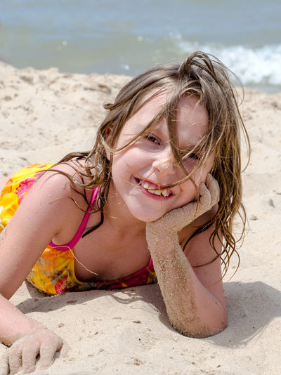 Close-up portrait of smiling girl on beach