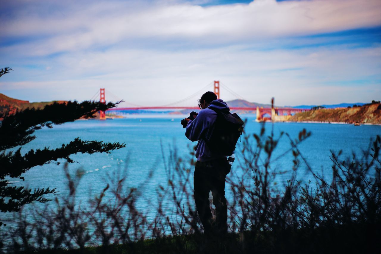 Man photographing at shore with golden gate bridge in background