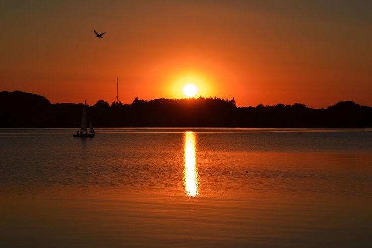 Scenic view of ratzeburger see lake against orange sky