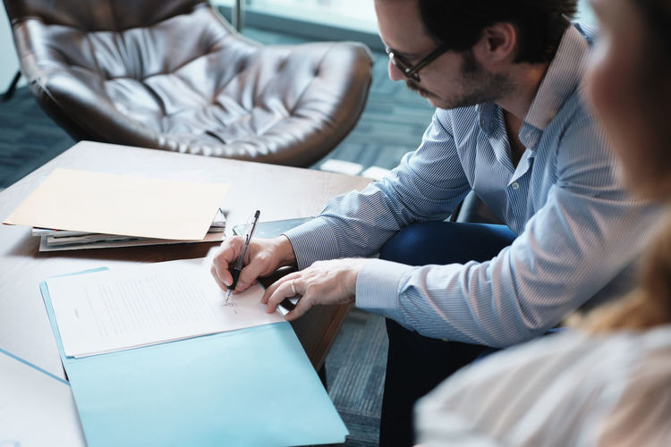 High angle view of businessman signing document while sitting with coworker in office