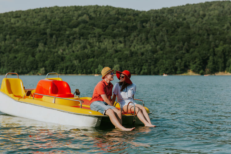 Cheerful Man And Woman In Paddleboat On Lake Against Sky