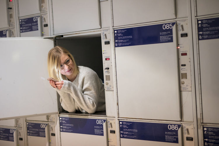Young Woman Holding Mobile Phone In Locker