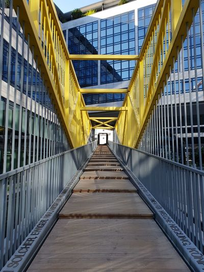 bridge Peaceful Lookingup Architecture Symmetrical Architecture No People Lines And Shapes Stairs Happiness Sunny Yellow Lines The Architect - 2018 EyeEm Awards The Great Outdoors - 2018 EyeEm Awards Words Letters Typography Shadow And Light Yellow City Architecture Built Structure Footbridge Bridge Arched Cable-stayed Bridge vanishing point The Way Forward Entryway Bridge - Man Made Structure Narrow Diminishing Perspective