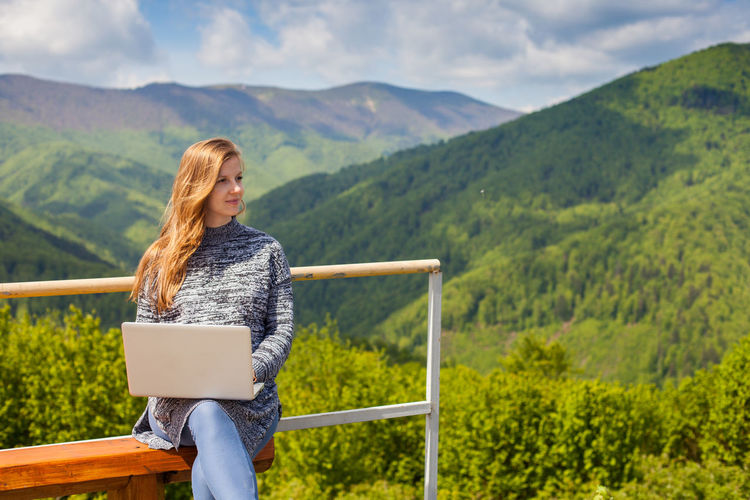 Thoughtful woman using laptop while sitting on bench against mountains