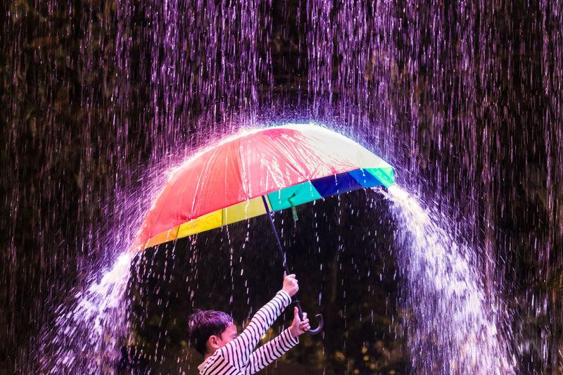 Boy spinning umbrella during rainy season