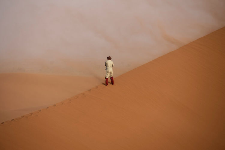 Real People Desert One Person Landscape Sand Dune Scenics - Nature Land Arid Climate Lifestyles Nature Climate Full Length Sand Sahara Desert NOMAD Man Morocco Orange Color