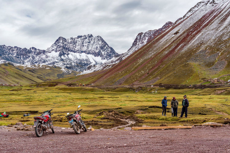 Men with bicycle on mountain against sky