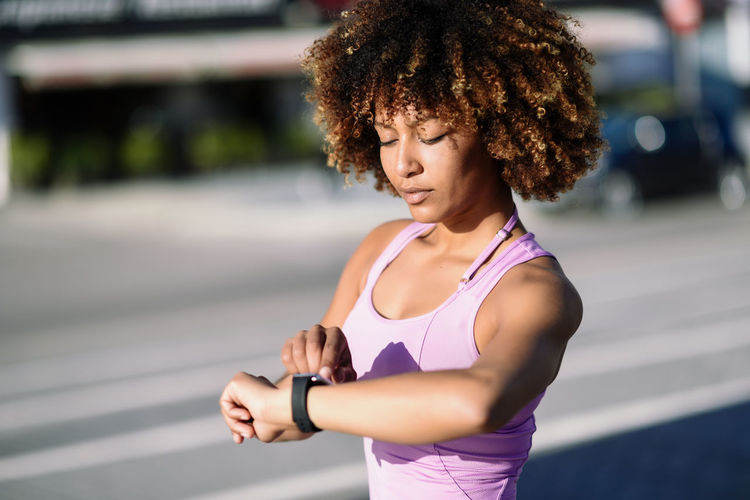 Young black woman using smartwatch touching touchscreen in active sports activity. Girl with afro hair looking at her smart watch screen. Woman Digital Display Examining Exercising Female Fitness Girl Healthy Lifestyle Jogging Lifestyles Outdoors Runner Smart Watch Smartwatch Sport Sports Training Stopwatch Street Technology Touch Screen Watch Wearable Computer Wristwatch Young Adult Young Women