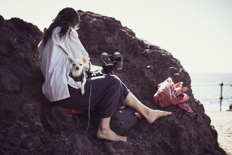 Friends sitting on rock by sea against sky