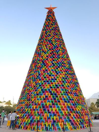 Giant Christmas tree made of plastic chairs in Monterrey Monterrey Mexico Monterrey Mexico Multi Colored Celebration Tradition Sky Christmas Ornament Christmas Decoration christmas tree Celebration Event Decorating The Christmas Tree Carnival - Celebration Event Tree Topper Pyramid Shape Christmas Lights Christmas Christmas Bauble