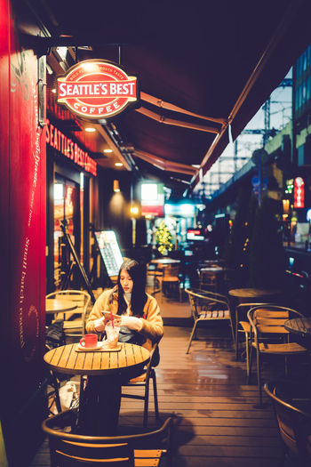 Chairs and tables at sidewalk cafe in city at night