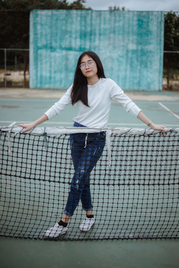 Portrait of young woman leaning on tennis net while standing at court