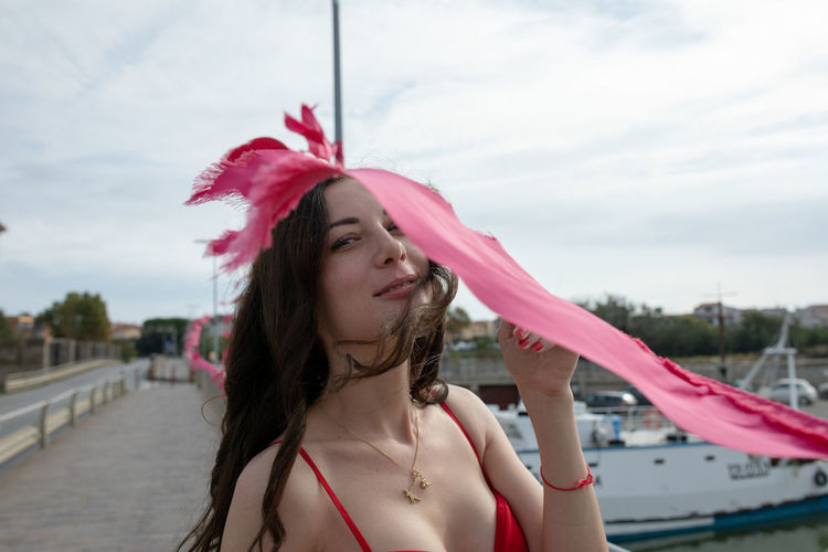 Portrait of smiling woman standing by pink flag at harbor