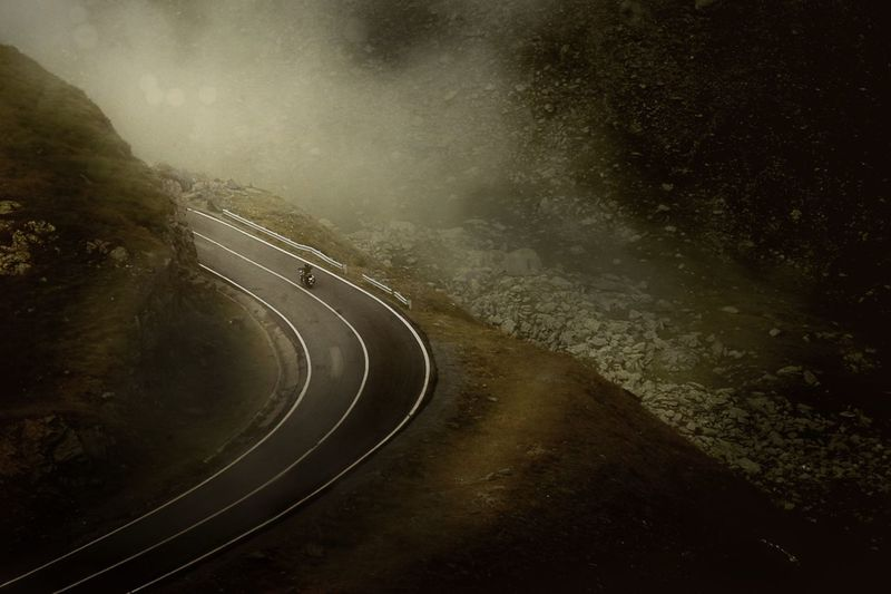 High angle view of man riding motorcycle on road in foggy weather