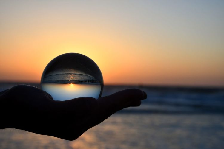 Cropped hand of person holding crystal ball against sea and sky during sunset