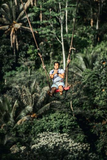 Full length of man on swing in forest