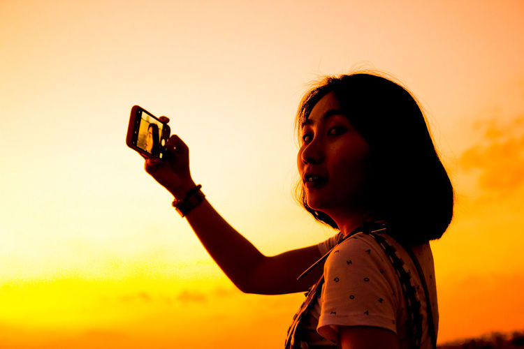 Portrait of young woman photographing with smart phone against sky during sunset